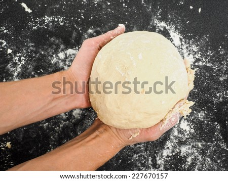 Person holding a proof dough over black table with flour mess - stock photo