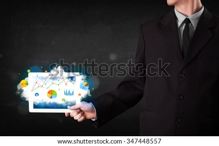 Person holding a white touchpad with cloud technology and charts - stock photo