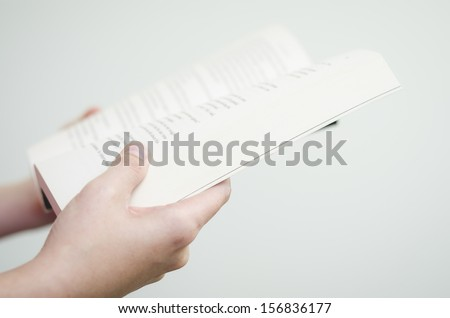 Person holding an open book - stock photo