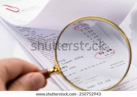 Person Holding Magnifying Glass On Receipt With Red Circle Made On Total Amount - stock photo