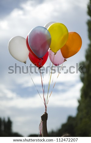 person holding multi colored helium ballons - stock photo