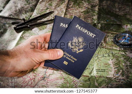 person holding passports with a map and compass in the background - stock photo