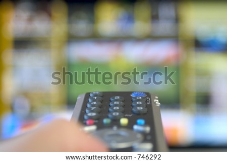 person holding remote ontrol in front of TV - stock photo