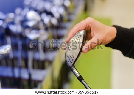 Person holding with hand golf club in a Golf Shop. Closeup photo - stock photo
