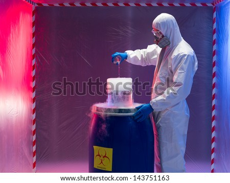 person in a protective suit and gas mask experimenting with steaming substances over a blue plastic waste container inside a containment tent - stock photo