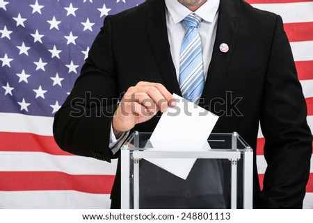Person In Front American Flag Putting Ballot In Glass Box - stock photo