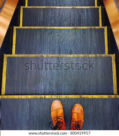 Person in orange boots going down on the escalator. - stock photo