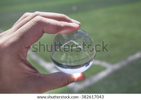 Person in soccer field holding glass sphere. - stock photo