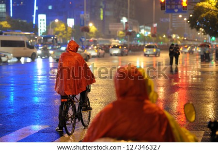 Person on bike covered with red poncho waiting at crossroads. Rainy night. Shanghai China - stock photo