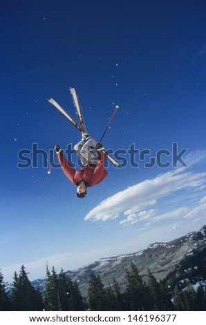 Person on skis jumping against trees and blue sky - stock photo