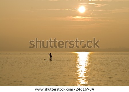 person paddling in sunset - stock photo