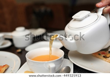 Person pouring buckthorn tea in a cafe - stock photo