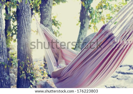 Person relaxing in a hammock in the shade of a tree on a hot summer day, view from behind. With retro filter effect. - stock photo