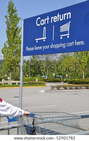 Person return shopping cart with cart reture sign - stock photo