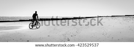 Person riding a bike on the beach by the water. Black and white silhouette. Copy space - stock photo