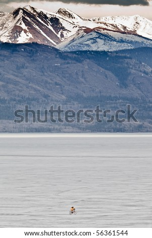 Person riding a bike on vast frozen lake - stock photo