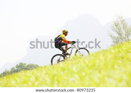 Person riding a bike up hill style - stock photo