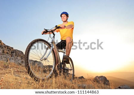 Person riding a mountain bike on a sunset, low angle view - stock photo