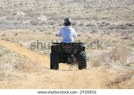 Person riding four wheeler ATV on trail from behind - stock photo