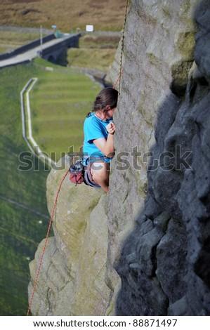Person rock climbing outdoors - stock photo
