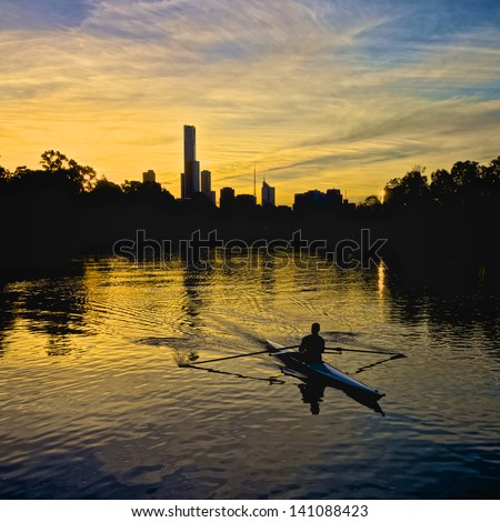 Person rowing on the Yarra river with the Melbourne city skyline in the background - stock photo