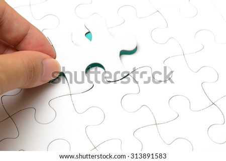 Person's hand completing last piece of Jigsaw puzzles - stock photo
