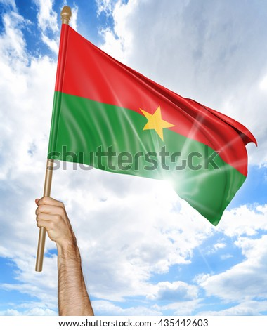 Person's hand holding the Burkina Faso national flag and waving it in the sky, part 3D rendering - stock photo