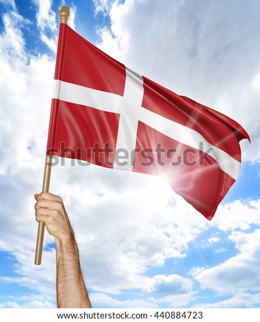 Person's hand holding the Danish national flag and waving it in the sky, 3D rendering - stock photo