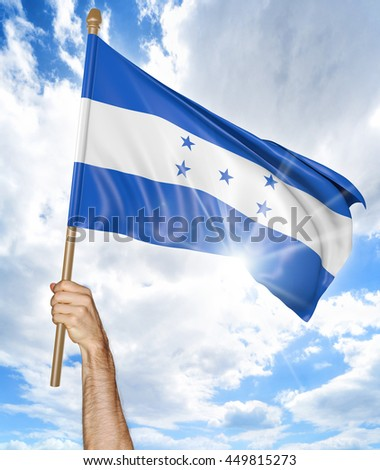 Person's hand holding the Honduran national flag and waving it in the sky, 3D rendering - stock photo
