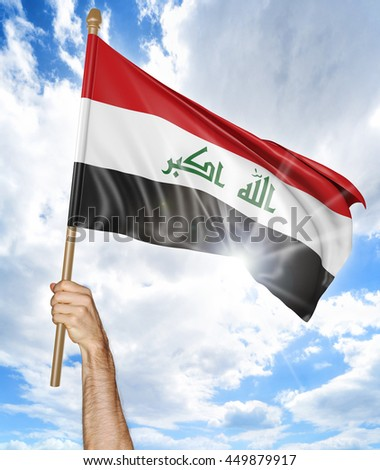 Person's hand holding the Iraqi national flag and waving it in the sky, 3D rendering - stock photo
