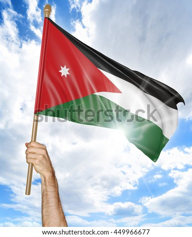 Person's hand holding the Jordanian national flag and waving it in the sky, 3D rendering - stock photo