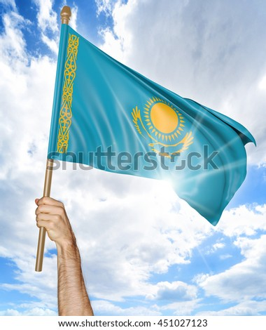 Person's hand holding the Kazakhstan national flag and waving it in the sky, 3D rendering - stock photo