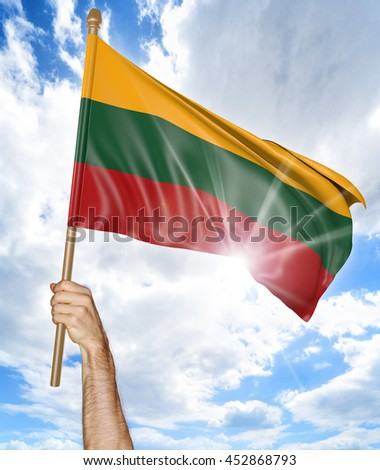 Person's hand holding the Lithuanian national flag and waving it in the sky, 3D rendering - stock photo