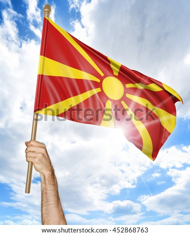 Person's hand holding the Macedonian national flag and waving it in the sky, 3D rendering - stock photo