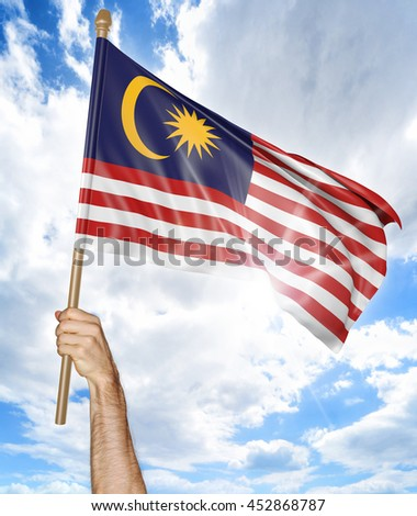 Person's hand holding the Malaysian national flag and waving it in the sky, 3D rendering - stock photo