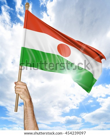 Person's hand holding the Niger national flag and waving it in the sky, 3D rendering - stock photo