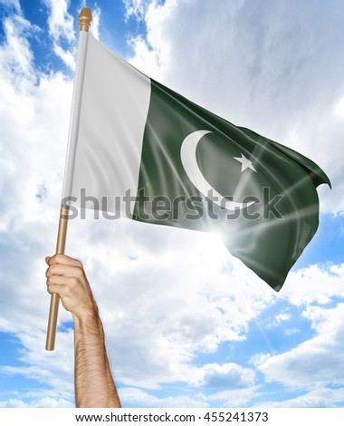 Person's hand holding the Pakistani national flag and waving it in the sky, 3D rendering - stock photo