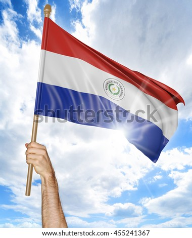 Person's hand holding the Paraguayan national flag and waving it in the sky, 3D rendering - stock photo