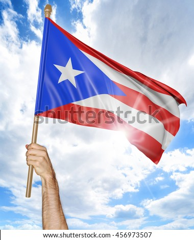 Person's hand holding the Puerto Rican national flag and waving it in the sky, 3D rendering - stock photo