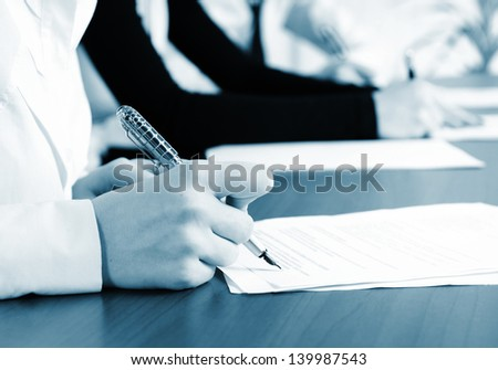 person's hand signing an important document - stock photo