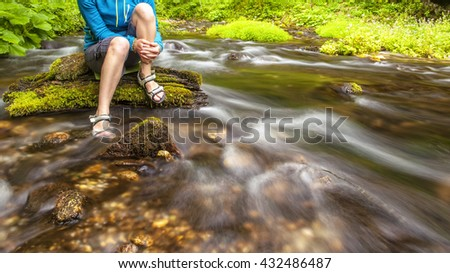 person sits on the stone covered with moss in the center of rapid flow of the river, holding his feet in clear water against the background of juicy greenery - stock photo