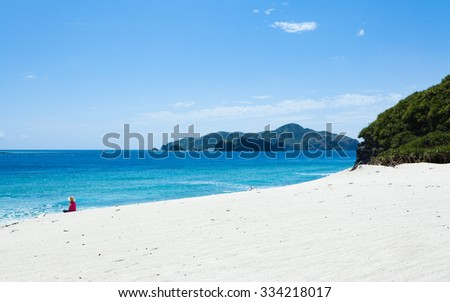 Person sitting on a tropical beach of a deserted tropical island with clear blue sea, Kerama Islands National Park, Okinawa, Japan - stock photo