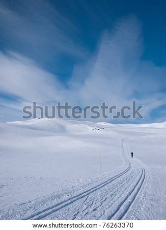 Person skiing alone in a groomed curved double ski track with characteristic clouds in the background in the norwegian mountains at easter - stock photo