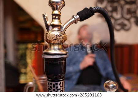 Person smoking nargile in the asian restaurant - stock photo