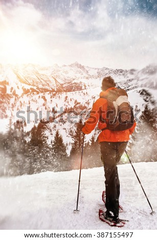 Person snow trekking standing on an alpine summit overlooking snow covered forested mountains and valleys below lit by the glow of the morning sun - stock photo