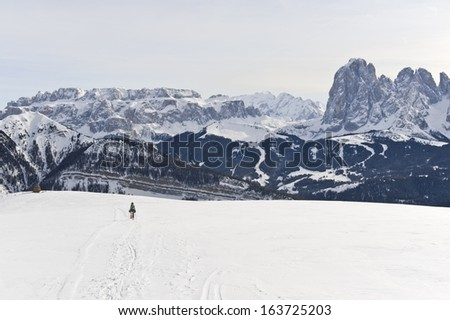 Person snowshoeing against wide Dolomites landscape - stock photo