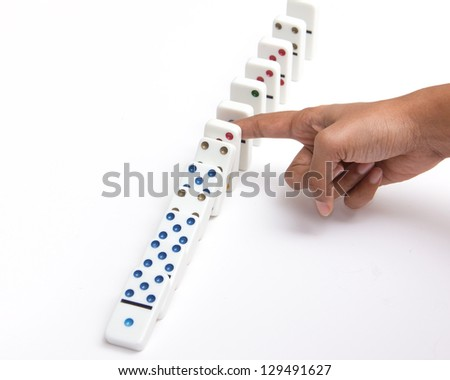 Person stopping the dominoes from falling - stock photo