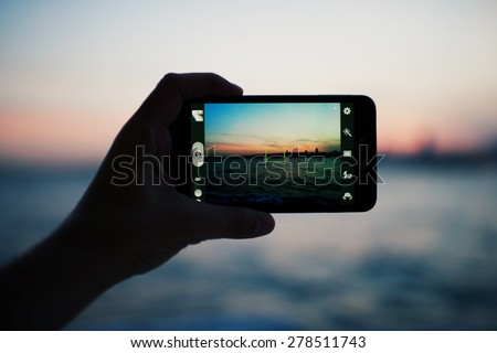 Person taking a photo of amazing sunset using smart phone camera, tourist hand holding cell phone while taking a photograph of nature landscape in travel,taking a picture of outdoors, blur background - stock photo