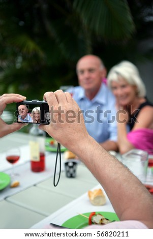 Person taking a picture of a couple of senior - stock photo