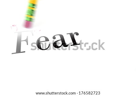 Person using a pencil eraser to erase fear from their life so they can start new - stock photo